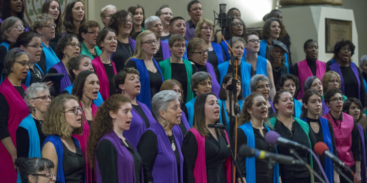 choir in colorful vests singing