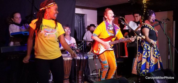 woman playing an electric guitar with African dancers