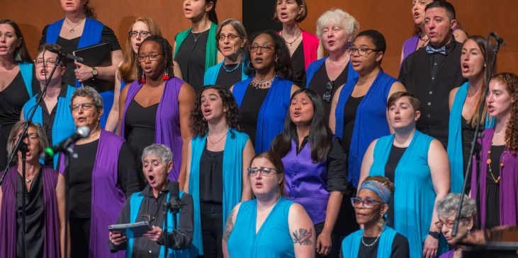 a diverse group of people singing wearing jewel toned vests